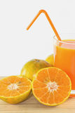 Slices of orange with orange juice fresh in glass. Slices of orange with orange juice fresh in glass isolated on wooden table white background Royalty Free Stock Photos
