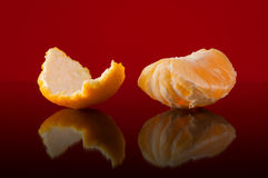 Slices of orange and peel on a red background Stock Photo