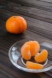Slices of orange and a ripe tangerine in  glass saucer. Against the background  the old wooden table. Slices of orange and a ripe tangerine in a glass saucer Royalty Free Stock Image