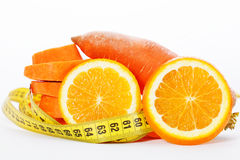 Slices of orange with slices of carrot and measuring tape Royalty Free Stock Image
