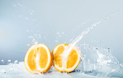 Slices of orange thrown water. Halves of orange thrown water against the light blue background Stock Photography