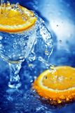 Slices of orange in water. Two slices of orange and a glass in blue clean water Stock Image