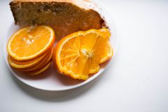Pieces of orange on a plate next to a piece of cake stock photos
