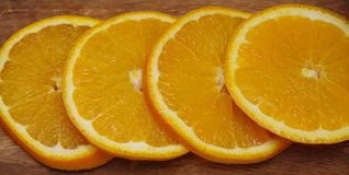Slices of orange on a wooden background. Four slices of orange on a wooden brown background Royalty Free Stock Image