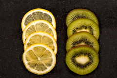 Slices of oranges and kiwi. On a dark surface Stock Image