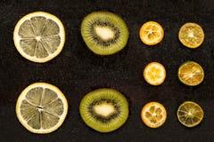 Slices of oranges, lemon and kiwi. On a dark surface Royalty Free Stock Photos