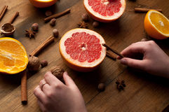 Slices of oranges, lemons and grapefruits on vintage wood table. Citrus fruit with star anise, cinnamon. healthy eating with natur. Al vitamins. holding hands in royalty free stock photo