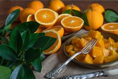 Slices of oranges on a plate. Oranges fruits and orange leaves on a kitchen table, rustic background royalty free stock image