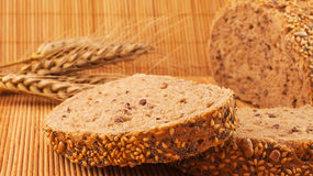 Slices of organic bread decorated with natural cereals on wooden background and wheat Royalty Free Stock Image