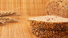 Slices of organic bread decorated with natural cereals on wooden background and wheat. Slices of organic bread decorated with natural cereals Stock Image