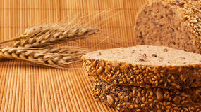 Slices of organic bread decorated with natural cereals on wooden background and wheat. Slices of organic bread decorated with natural cereals Royalty Free Stock Image