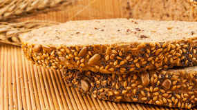 Slices of organic bread decorated with natural cereals on wooden background and wheat Stock Images