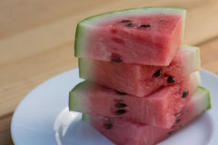 Slices of Organic California grown Watermelon stacked on a white plate on a wooden table. Royalty Free Stock Photo