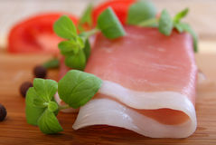 Slices of parma ham. With red tomato and oregano stock photography