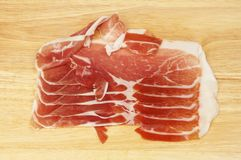 Parma ham on a board. Slices of parma ham on a wooden chopping board Royalty Free Stock Photos