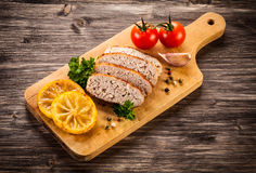 Slices of paté on a cutting board with seasonings Stock Photography