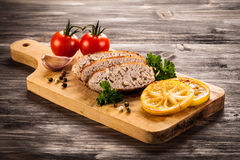 Slices of paté on a cutting board with seasonings Royalty Free Stock Photos