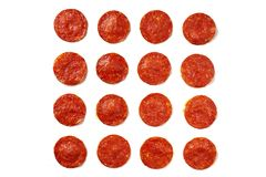 Slices of pepperoni sausage on a white background. To edit. Ingredient for the preparation of classic Pepperoni pizza. Sharp sausages Stock Image