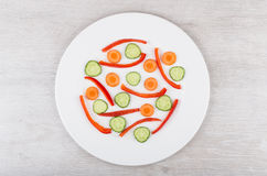 Slices of peppers, carrots and cucumbers in white glass plate. On wooden table. Top view Stock Photos
