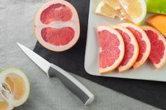 Slices and pieces of fresh grapefruit in a white plate with a knife for cutting on textile background stock photos