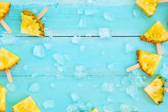 Slices pineapple popsicle sticks with ice on wood plank blue color. Summer fruit backgrond concept, top view, copy space royalty free stock images