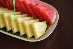 Slices of pineapple and watermelon on a table Stock Photos