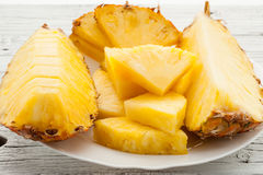 Slices of a pineapple on white wooden background Royalty Free Stock Image