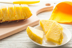 Slices of a pineapple on white wooden background Stock Photos