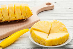 Slices of a pineapple on white wooden background Stock Photography