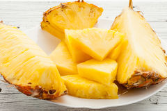 Slices of a pineapple on white wooden background Royalty Free Stock Images