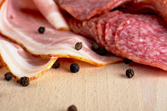 Slices of pink bacon and salami with black peppercorn on wooden Royalty Free Stock Images