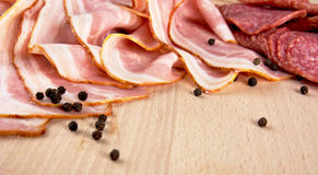 Slices of pink bacon and salami with black peppercorn on wooden Stock Photos