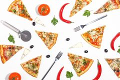 Slices of pizza, ingredients and cutlery on a white background. Top view royalty free stock photos