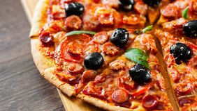 Slices of Pizza with Mozzarella cheese, salami, pepper, pepperoni, Tomatoes, olives, Spices and Fresh Basil. Italian pizza on wood Royalty Free Stock Photos