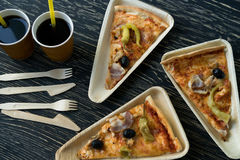 A slices of pizza is on a wooden plate. Royalty Free Stock Image