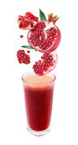 Slices of pomegranate fall into a glass of fresh j Stock Image