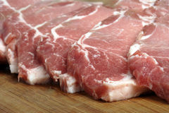 Slices of pork. Slices of fresh pork on a chopping board Stock Photos