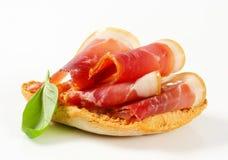 Slices of prosciutto on crispy bread Stock Photos