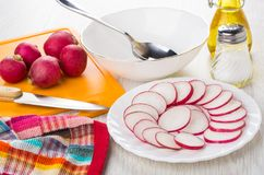 Slices of radish, cutting board, knife, vegetable oil, salt, bow. Slices of radish in plate, cutting board, knife, vegetable oil, salt, empty bowl and spoon on Royalty Free Stock Photography