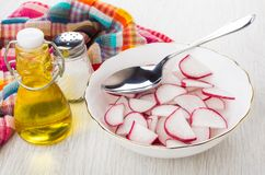 Slices of radish and spoon in bowl, vegetable oil, salt. And napkin on wooden table Royalty Free Stock Photo