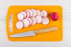 Slices of radishes and kitchen knife on orange cutting board. On wooden table. Top view Stock Photography