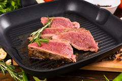 Slices of Rare Beef Sizzling on Cast Iron Fry Pan Stock Images