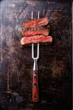 Slices of Rare beef steak on meat fork royalty free stock photos