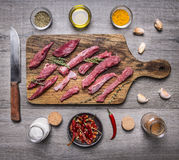 Slices of raw beef with herbs and garlic on a cutting board with a knife and spices on wooden rustic background top view close up. Slices of raw beef herbs and Royalty Free Stock Images