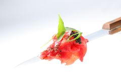 Slices of raw beef on knife. Thin slices of raw beef on knife Stock Image