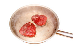 Slices of raw beef are roasted on a steel pan. Insulated Stock Photo