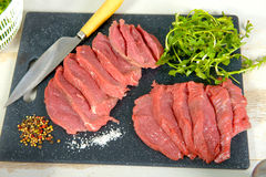 Slices of raw beef with salad. Slices of raw beef with a salad Stock Photography