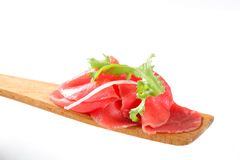 Slices of raw beef on spatula. Thin slices of raw beef on wooden spatula Royalty Free Stock Image