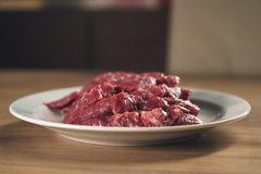 Slices of raw beef in white plate on kitchen table. Closeup photo Stock Image