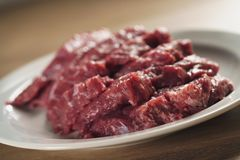 Slices of raw beef in white plate on kitchen table. Closeup photo Stock Photo